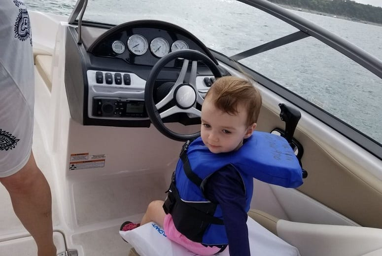 Small Boy Driving A Boat